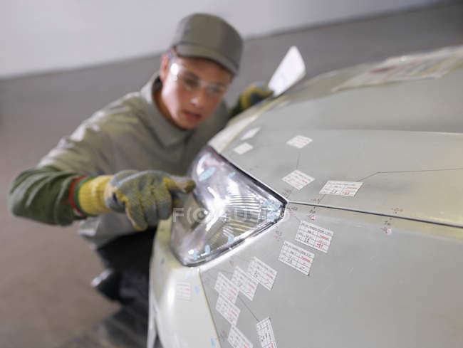 Travailleur de l'usine inspectant phare sur la voiture — Photo de stock