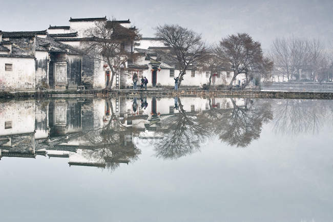 Mirror image of bare trees and traditional houses by lake, Hongcun Village, Anhui Province, China — Stock Photo
