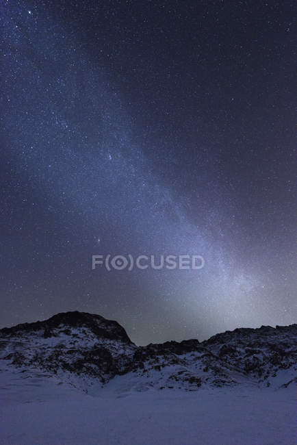 Rugged mountain on snow covered landscape underneath starry night sky, Kleifarvatn, Iceland — Stock Photo