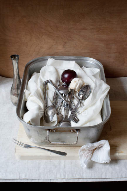 Cheesecloth with utensil and ripe plum in tray — Stock Photo