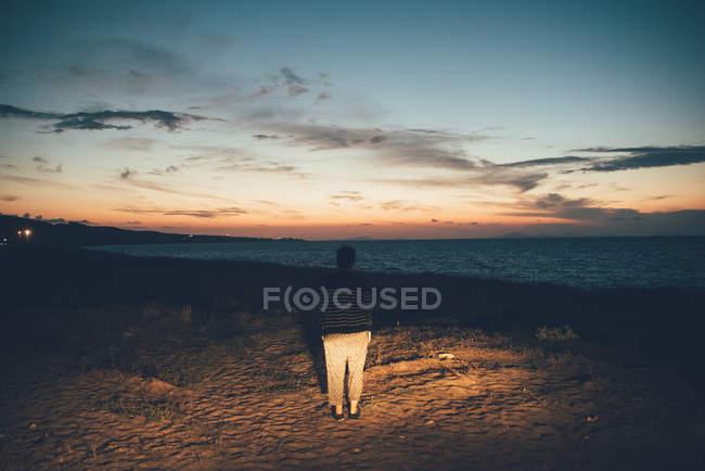 Vista posteriore della donna sulla spiaggia guardando il tramonto, Sorso, Sassari, Italia — Foto stock