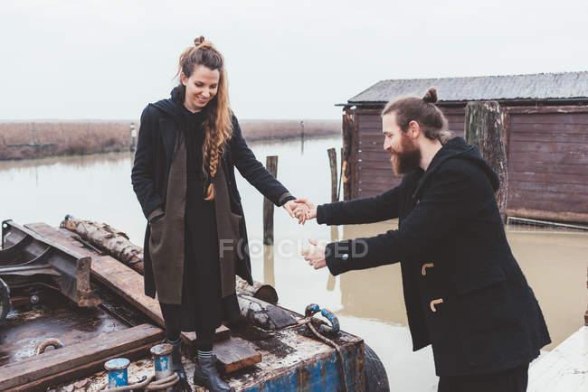Mann, die Freundin von Lastkahn auf Kanal Wasser hilft — Stockfoto