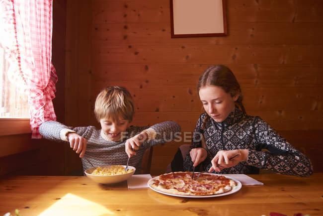 Adolescente et frère mangeant des pâtes et la pizza à la table de chalet — Photo de stock