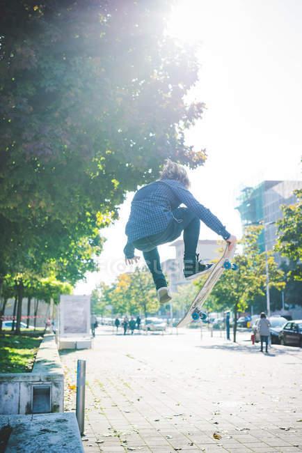 Junge männliche Skater Skateboard Sprung auf Bürgersteig zu tun — Stockfoto