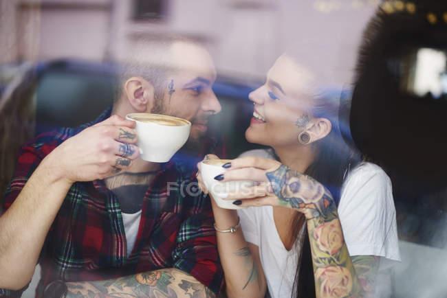 Вид через окно пара в кафе улыбающееся лицо — стоковое фото