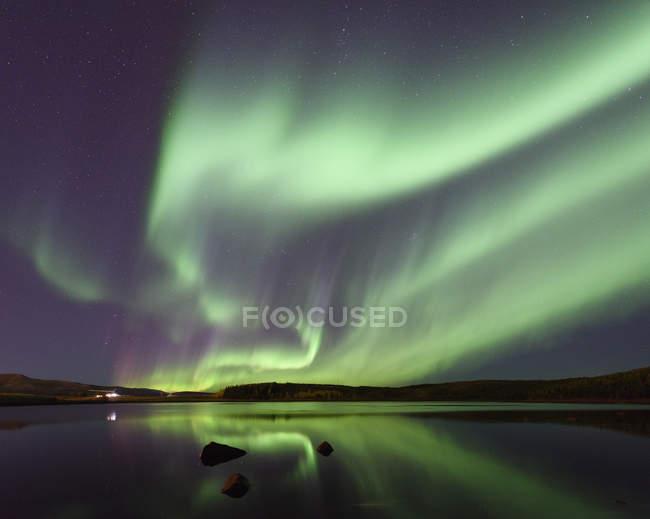 Aurora borealis reflecting in lake water at night — Stock Photo