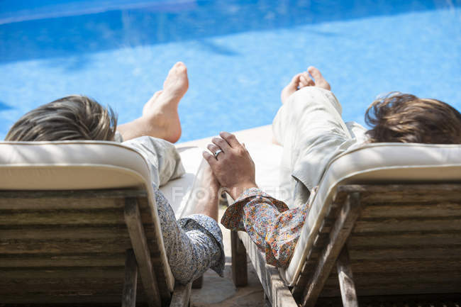 Rear view of romantic male couple holding hands at poolside — Stock Photo