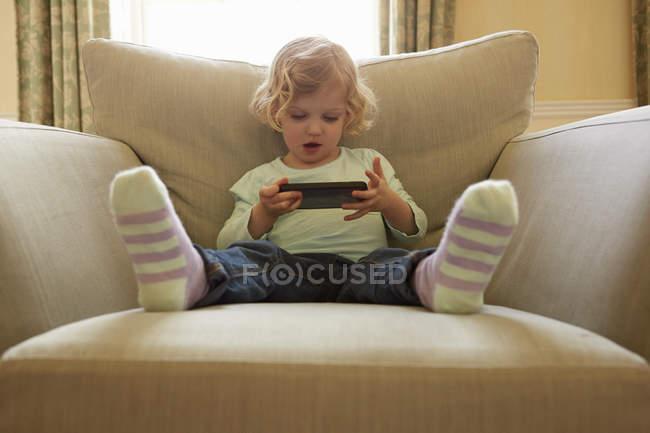Женский малыш сидит на кресле, играя в ручную компьютерную игру — стоковое фото