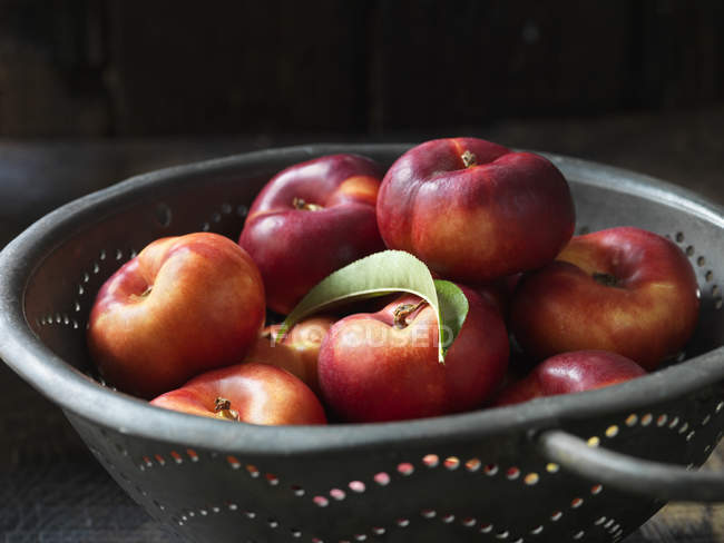 Fresh organic donut nectarines with leaf in colander — Stock Photo