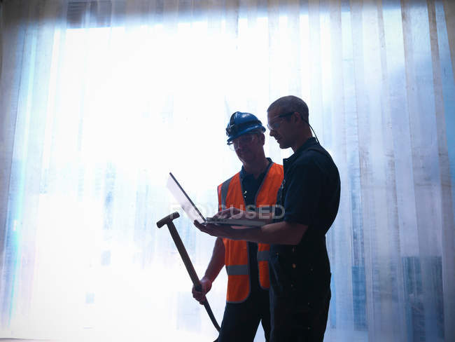 Silhouette of workers with laptop and spade - foto de stock