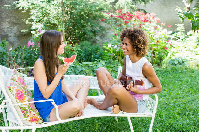 Smiling women relaxing in backyard — стокове фото
