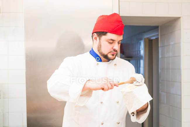 Baker cuillère glaçage dans un sac de tuyauterie — Photo de stock