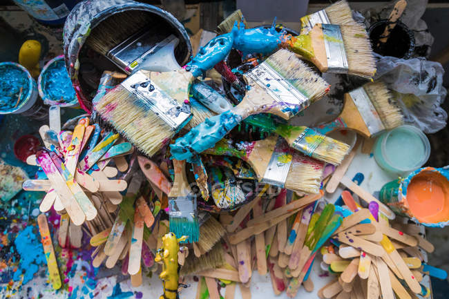 Top view of paint brushes and stirers in surfboard maker workshop — стоковое фото