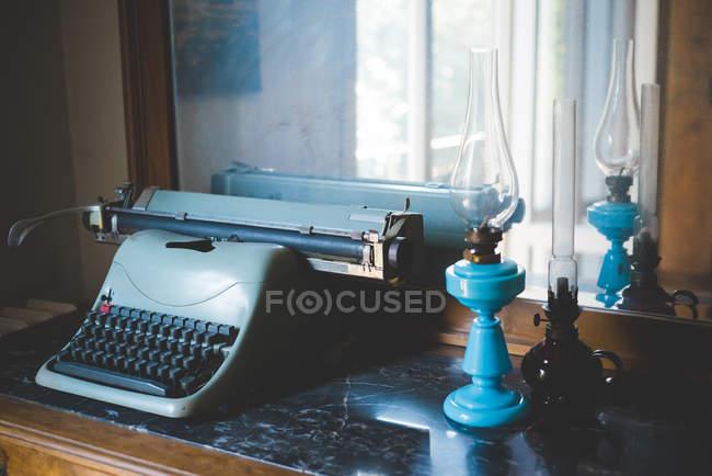 Vintage máquina de escrever e lâmpadas de óleo na mesa — Fotografia de Stock