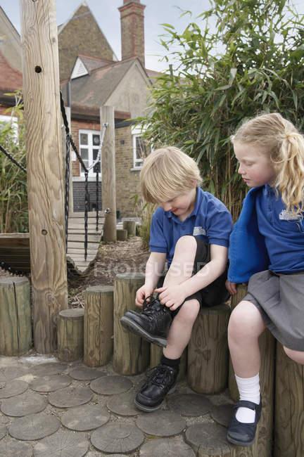 Школьница смотрит, как мальчик завязывает шнурки на бревенчатом заборе — стоковое фото