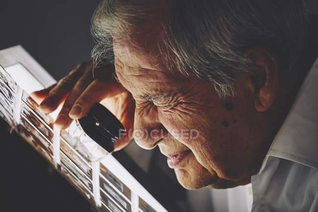 Senior homme regardant la feuille de diapositives de film avec loupe — Photo de stock
