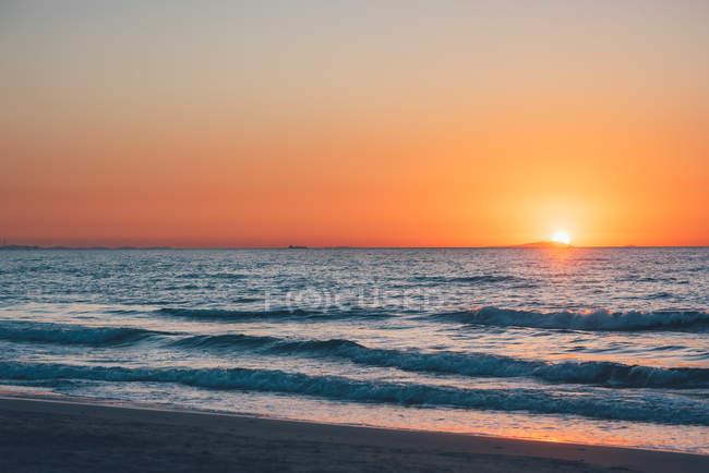 Coucher de soleil dans un ciel orange spectaculaire sur la mer — Photo de stock