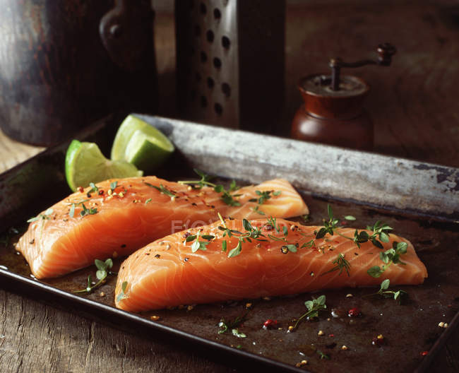 Raw salmon with lime wedges, herbs and seasoning on baking tray — Stock Photo