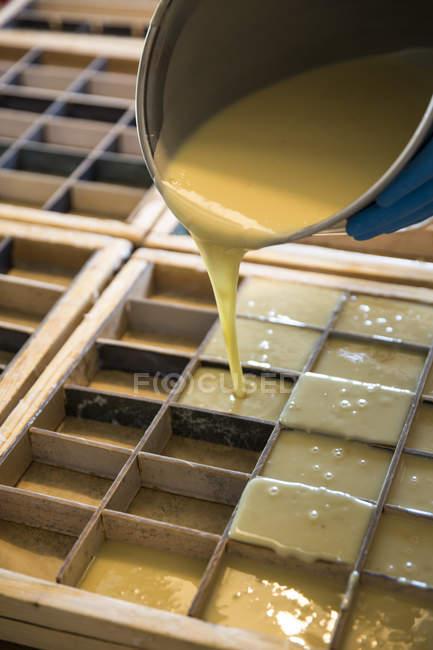 Casserole versant du savon de lavande liquide dans des moules dans un atelier de savon fait main — Photo de stock