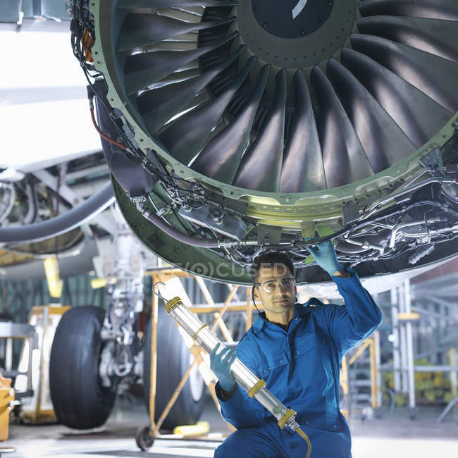 Portrait of engineer working on engine in aircraft maintenance factory — Stock Photo
