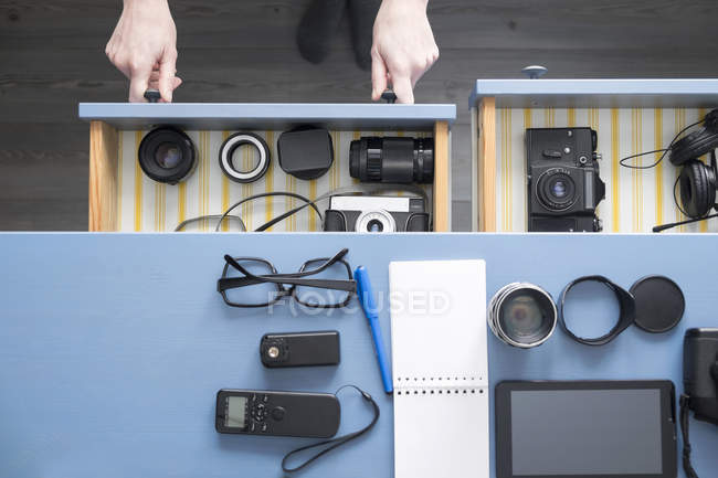 Overhead view of female photographers hands opening desk drawer in studio — Stock Photo