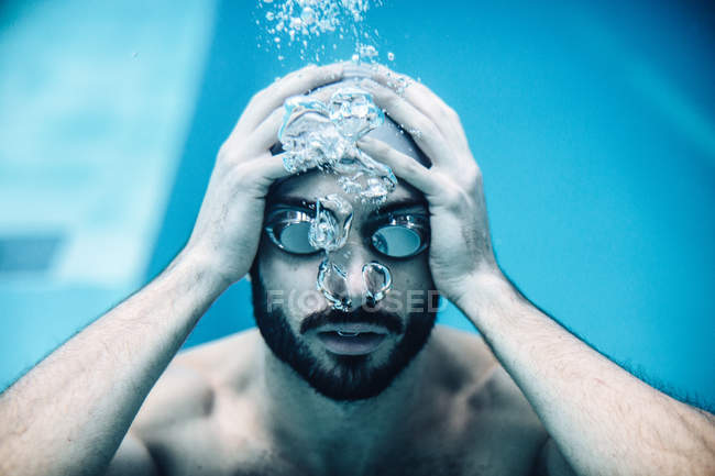 Underwater view of man in swimming pool blowing bubbles from nose — Stock Photo