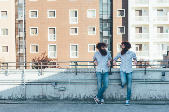 Identical male hipster twins chatting on apartment roof terrace — Stock Photo