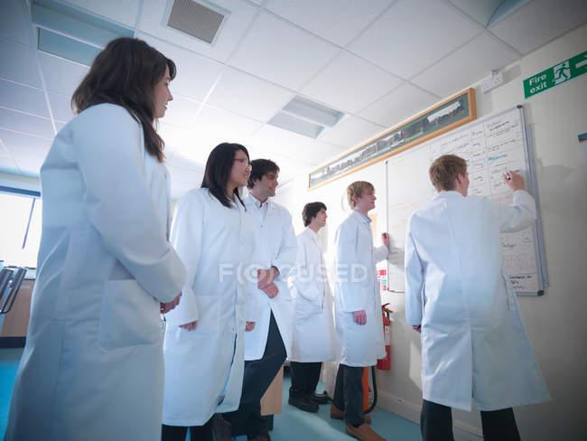 Estudiantes de ciencias escribiendo en pizarra en el laboratorio escolar - foto de stock