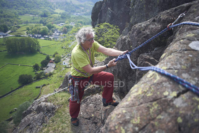 Rock climber on rock face preparing climbing rope — Stock Photo
