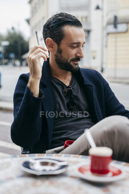 Mid adult man smoking cigarette at sidewalk cafe — Stock Photo