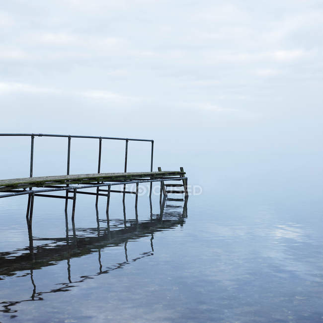 Wooden bridge over still lake reflecting in water — Stock Photo