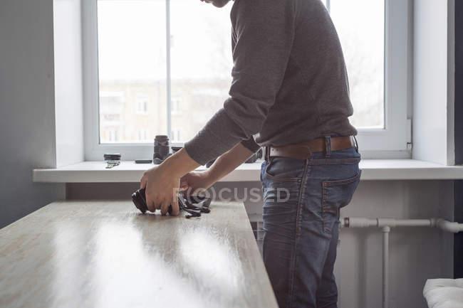 Male photographer checking camera on studio desk — Stock Photo