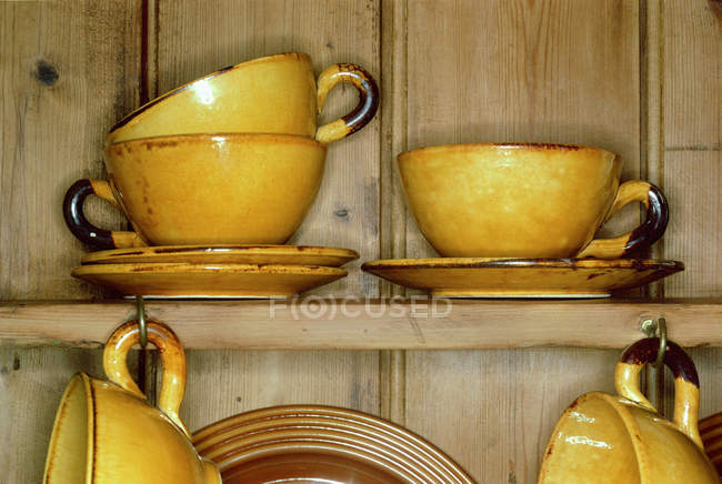 Yellow cups and saucers in cupboard — Stock Photo