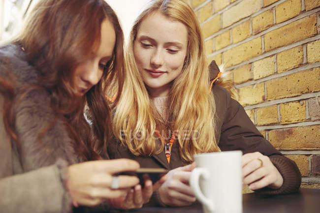 Dos amigas, sentadas al aire libre, tomando café, mirando el smartphone - foto de stock