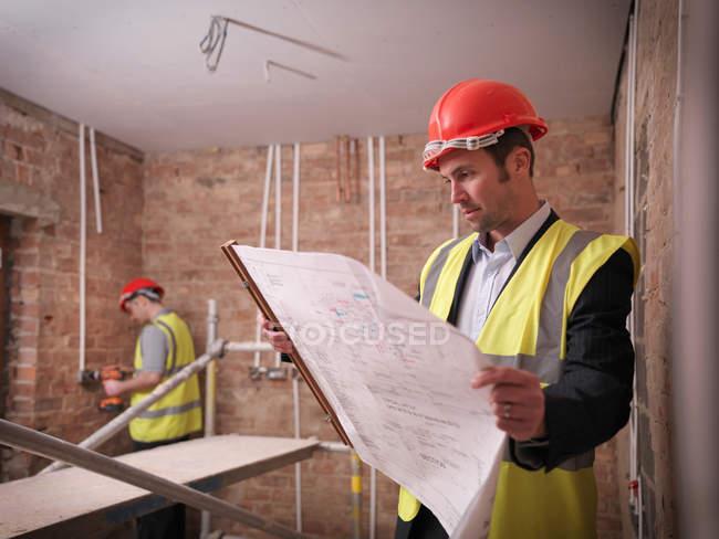 Архитектор с планами по строительству — стоковое фото
