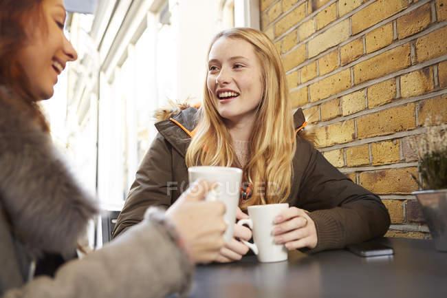 Due giovani donne che bevono caffè all'aperto — Foto stock