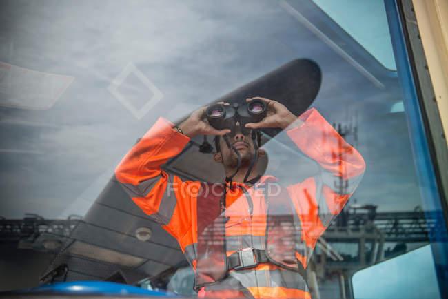 Matrose auf Schlepper blickt durch Fernglas — Stockfoto