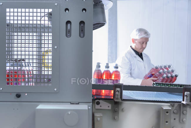 Worker inspecting water bottle on production line in spring water factory — Stock Photo
