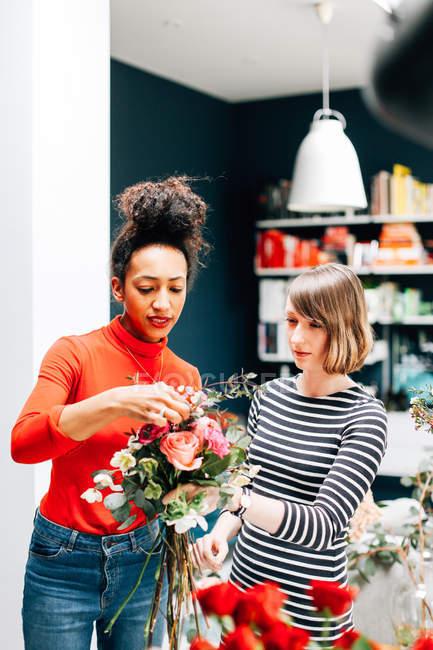 Дві жінки, що роблять букет в флористи магазин — стокове фото