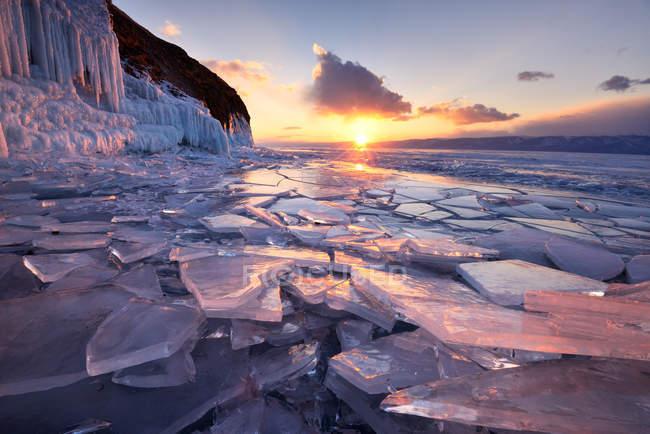 Ghiaccio rotto sulla riva del lago con cielo nuvoloso al tramonto — Foto stock