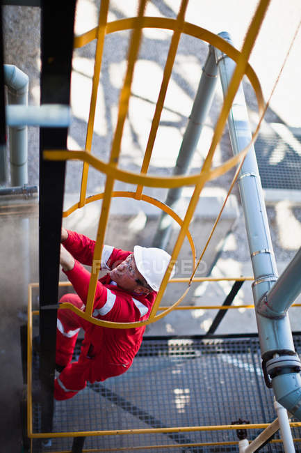 Worker climbing ladder at oil refinery — Stock Photo