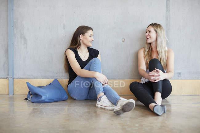 Двоє молодих школярок, які сидять на підлозі, розмовляють у вищому навчальному закладі. — стокове фото