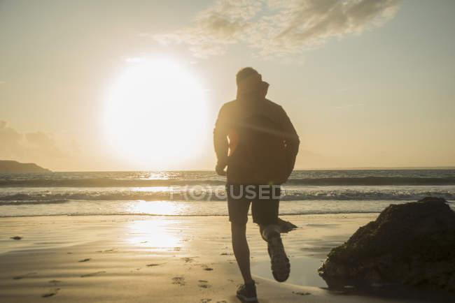 Vista trasera del hombre maduro corriendo a lo largo de la playa - foto de stock