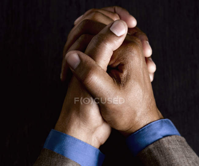 Hands of businessman in formal wear clasped together — Stock Photo