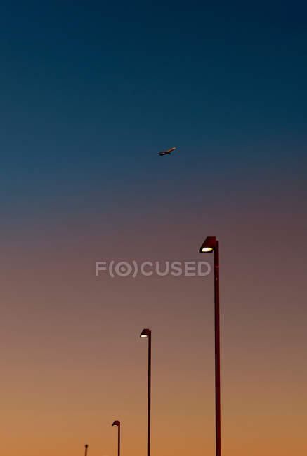 Airplane over street lights — Stock Photo