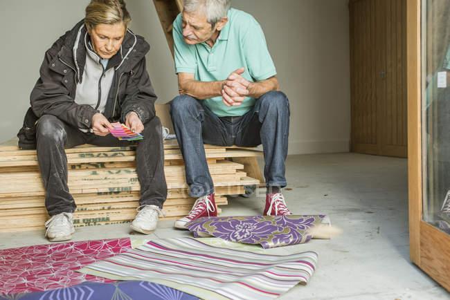 Senior couple making decision on wallpaper — Stock Photo