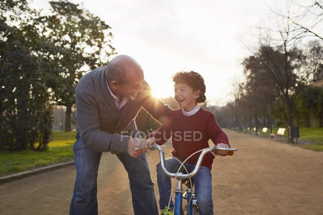 Grand-père enseignant petit-fils à faire du vélo dans le parc — Photo de stock