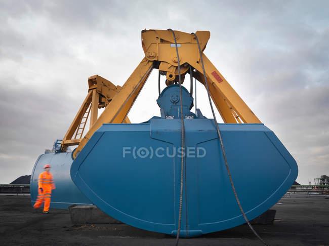 Портовый рабочий и тяжелое машиностроение — стоковое фото