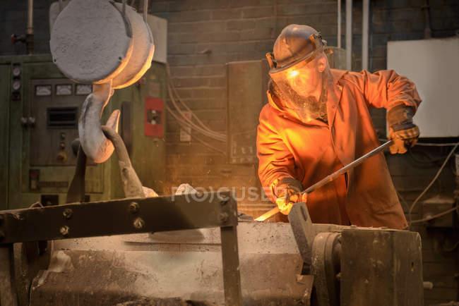 Worker raking molten steel in foundry — Stock Photo