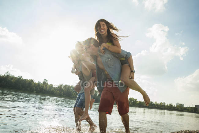 Young men giving young women piggy backs — Stock Photo